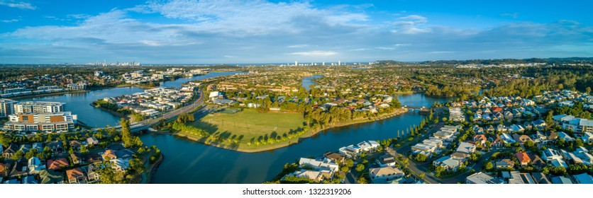 Aerial panorama of Varsity Lakes suburb, Reedy Creek and Lake Orr at sunset. Gold Coast, Queensland, Australia