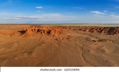 Aerial panorama view of the Bayanzag flaming cliffs at sunset in Mongolia, found in the Gobi Desert.
