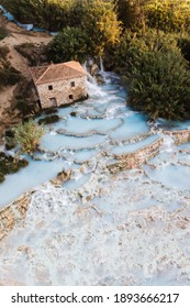 Aerial panorama view of famous Saturnia Hot Springs embedded in landscape during a beautiful tranquil morning at sunrise in summer, province of Grosseto, Tuscany, Italy - Shutterstock ID 1893666217