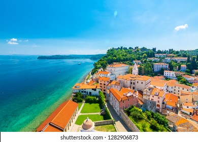 Aerial panorama view of Piran city, Slovenia. Look from tower in church. In foreground are small houses, Adriatic sea in background. Summer weather in famous tourist destination.