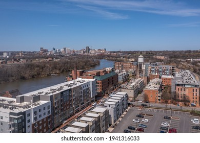 Aerial panorama view of Rocketts Landing near Manchester, Richmond Virginia, luxury apartment and condo building and regentrified industrial shopping complex along the James river with blue sky