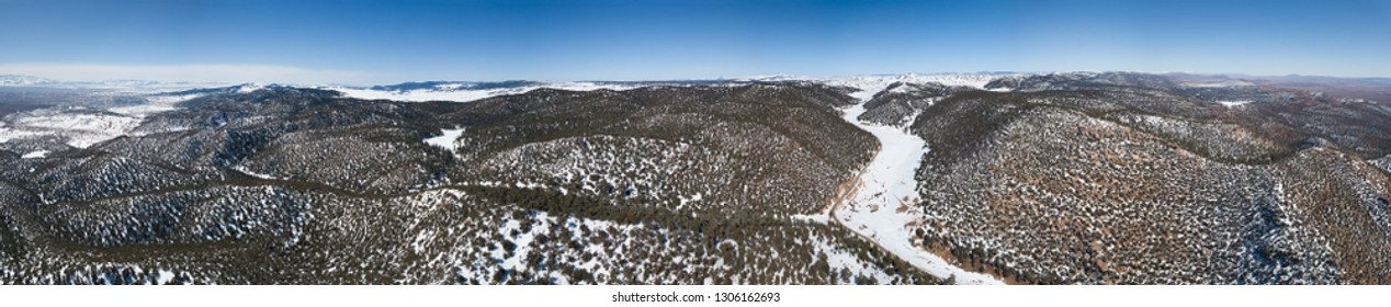Aerial panorama view of the snow-capped Atlas mountains covered with forest in Morocco at winter