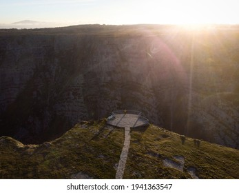 Aerial panorama view of tourist person in yellow jacket on viewing platform observation deck on cliff edge at Salto del Nervion river waterfall Delika Canyon Alava Araba, Basque Country Spain Europe