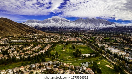 Aerial panorama of Yucaipa Valley with snow covered Little San Bernardino and San Gorgonio Mountains in the background on a winter day and golf course in the foreground