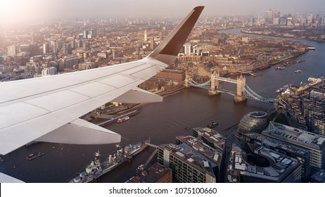 Aerial panoramic cityscape view of London and the River Thames with tower Bridge, Tower of London and City Hall with airplane wing in front, England, United Kingdom