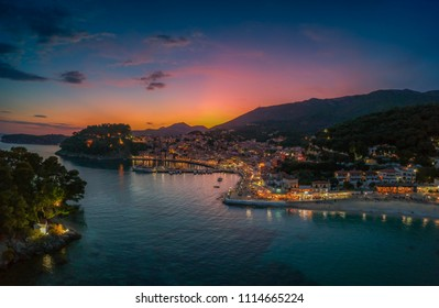 Aerial panoramic cityscape view of Parga city, Greece during the Summer. Beautiful architectural colorful buildings illuminated at night and night traffic near the port of Parga Epirus, Greece, Europe