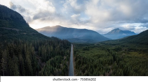 Aerial panoramic drone view of a scenic highway by the beautiful Canadian Landscape covered in clouds and fog. Taken in Vancouver Island, British Columbia, Canada.