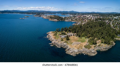 Aerial panoramic landscape view of a beautiful rocky shore on Pacific Coast. Taken in Saxe Point Park, Victoria, Vancouver Island, British Columbia, Canada.
