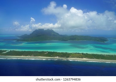 Aerial panoramic landscape view of the island of Bora Bora in French Polynesia with the Mont Otemanu mountain surrounded by a turquoise lagoon, motu atolls, reef barrier, and the South Pacific Ocean