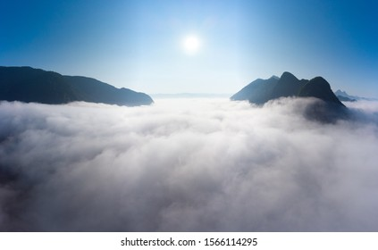 Aerial panoramic Nam Ou River drone flying over morning fog mist and clouds, Nong Khiaw Muang Ngoi Laos, dramatic landscape scenic pinnacle cliff, famous travel destination in South East Asia