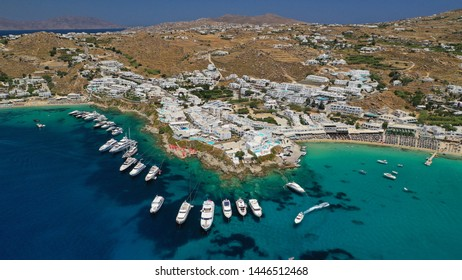 Aerial panoramic photo of famous turquoise clear sea celebrity sandy beach and bay of Psarou with yachts and sail boats in iconic island of Mykonos, Cyclades, Greece
