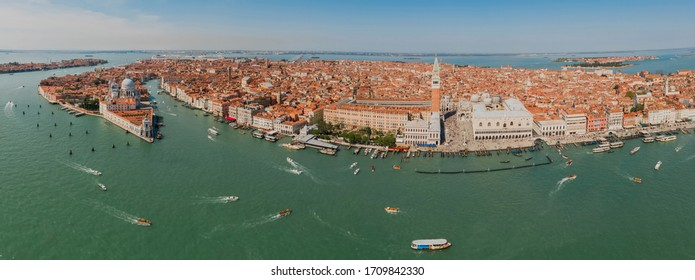 Aerial panoramic shot of Venice city and Grand Canal, Italy. View from above. Tiled roofs and nerros streets. Venetian atmosphere. Blue sky and lagoon water. Historical buildings.