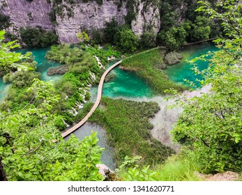 an aerial and panoramic vie of the wooden pathway between the colorful lakes of croatia