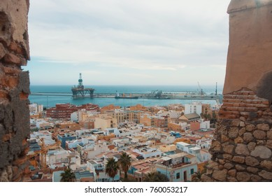 Aerial panoramic view of Almeria old town and port from the castle (Alcazaba of Almeria) over the mountain, Andalusia, Spain. Fortress walls at the foreground.