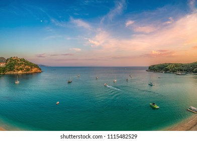 Aerial panoramic view of the amazing beach of Valtos at sunset. It is one of the longest beaches in the coastal town of Parga, Greece, located near the historical castle of Parga.