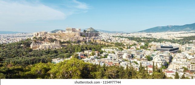Aerial panoramic view of Athens with Acropolis hill, Greece. Famous Acropolis is the main landmark of Athens. Scenic panorama of Athens city from above. Landscape of Athens on a sunny summer day.