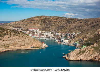 Aerial panoramic view of Balaklava bay in Crimea, mountain cliffs and sea with ships. Beautiful nature panorama landscape, town among hills and black sea coast from air, drone shot