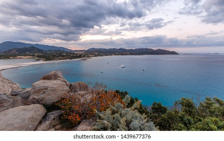 Aerial panoramic view of the beach and sea with azure turquoise crystal clear water, mountains in the background, in Villasimius, Sardinia (Sardegna) island, Italy. Holidays, best beaches in Sardinia.