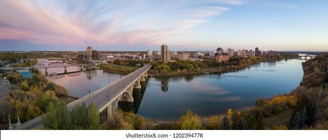 Aerial panoramic view of a bridge going over Saskatchewan River during a vibrant sunrise in the Fall Season. Taken in Saskatoon, SK, Canada.