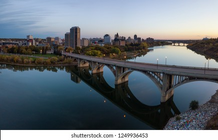 Aerial panoramic view of a bridge going over Saskatchewan River during a vibrant sunrise in the Fall Season. Taken in Saskatoon, SK, Canada.