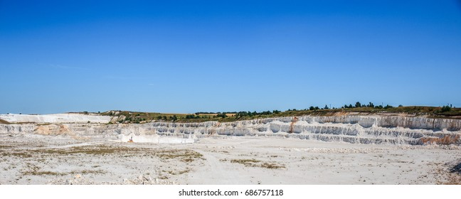 Aerial panoramic view of chalk or Cretaceous mining quarry. Open-cast quarry, limestone mining.