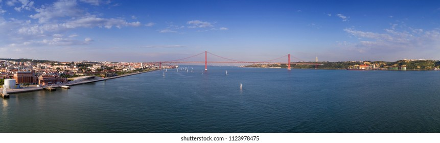 Aerial panoramic view of the city of Lisbon with sail boats on the Tagus River and the 25 of April Bridge (Ponte 25 de Abril) on the background; Concept for travel in Portugal and visit Lisbon