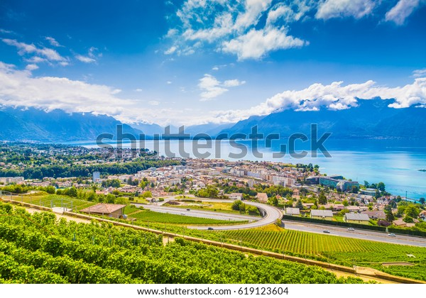Aerial panoramic view of the city of Vevey at Lake Geneva with vineyards of famous Lavaux wine region on a beautiful sunny day with blue sky and clouds in summer, Canton of Vaud, Switzerland