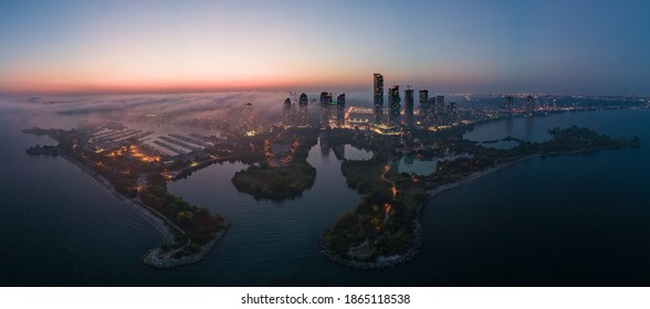 Aerial panoramic view of city waterfront highrise condo and business office buildings, constructions, marina, highways and roads by the lake halfway covered with fog at dusk.