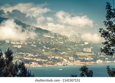Aerial panoramic view of the city of Yalta in Crimea, Russia. Landscape of the Southern coast of Crimea in summer. Scenic panorama of Crimea coastline with low lying clouds above Yalta.