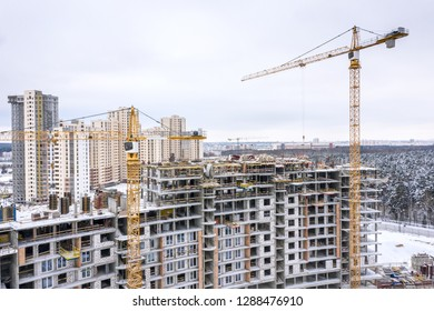 aerial panoramic view of construction city site in winter. yellow tower cranes building new residential apartments