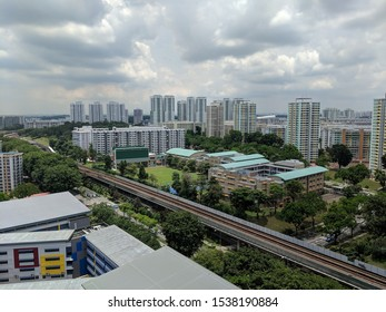 Aerial panoramic view dense of HDB apartment buildings at midday in neighborhood of Singapore. Singapore train metro in view.
