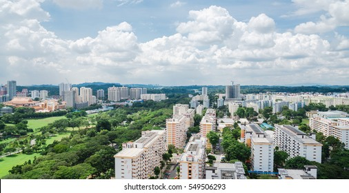 Aerial panoramic view dense of HDB apartment buildings at midday in Ang Mo Kio neighborhood, Singapore. High rises flat complex grass courtyard, green trees, tennis court, playground at blue cloud sky