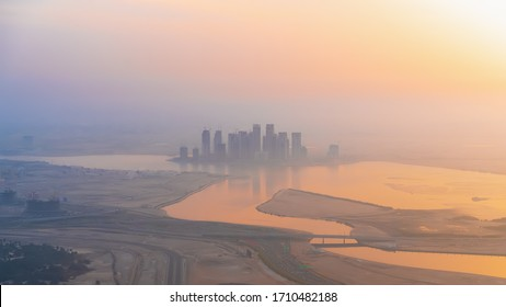 Aerial panoramic view of Dubai skyline in sunrise haze light from highest rooftop, UAE.