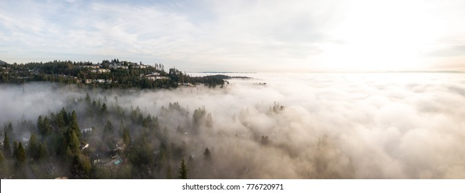 Aerial panoramic view of fog covered luxury homes on top of a hill. Taken in Horseshoe Bay, West Vancouver, British Columbia, Canada.