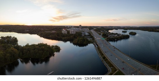 Aerial panoramic view of a Highway in the Modern City during a vibrant Sunset. Taken in Halifax, Dartmouth, Nova Scotia, Canada.