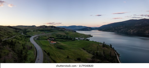Aerial panoramic view of a highway near Kalamalka Lake during a vibrant summer sunset. Located between Kelowna and Vernon, BC, Canada.