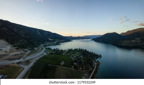 Aerial panoramic view of homes near a lake during a vibrant summer sunset. Located near Kelowna and Vernon, BC, Canada.