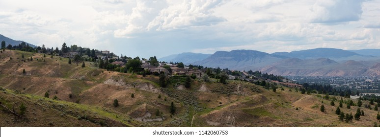 Aerial panoramic view of homes on top of a hill during a cloudy summer day. Located in Kamloops City, Interior BC, Canada.