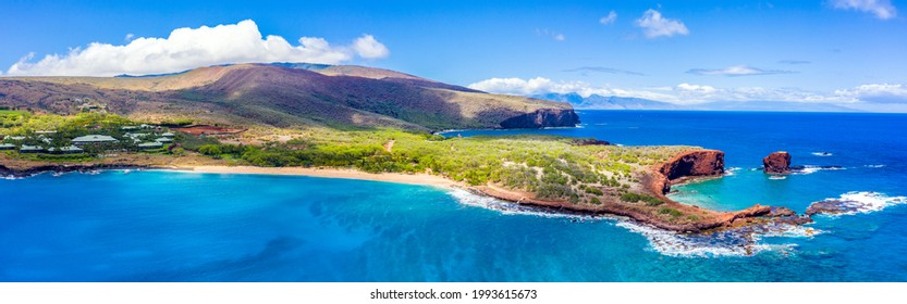 Aerial panoramic view of Lanai, Hawaii featuring Hulopo'e Bay and beach, Sweetheart Rock (Pu'u Pehe), Shark's Bay, and the mountains of Maui in the background.