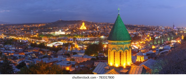 Aerial panoramic view of Old Town with dome of Lower Bethlemi Church and Sameba Holy Trinity Cathedral, Metekhi Church, bridge of Peace and Presidential Palace during evening blue hour, Tbilisi