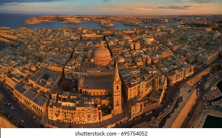 Aerial, panoramic view on historical Three cities over Valletta in golden light. Touristic destination. Historical centre of Malta island from the air. Stone monuments of Malta lit by the setting sun.
