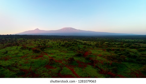 Aerial, panoramic view on Mount Kilimanjaro volcano, summit covered in snow lit by first sun rays with masai villages with circular fence in foreground. View from Amboseli national park border, Kenya.