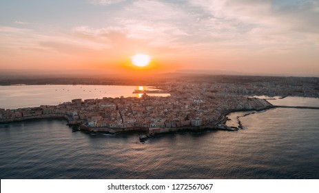 Aerial panoramic view of Ortigia island,old town of Syracuse.Small island on Sicily,Italy.Sicilian vacation,charming Italian experience.Beautiful seaside landscape at sunset