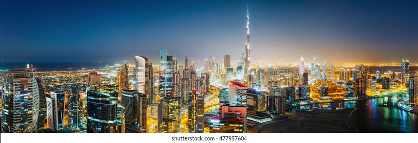 Aerial panoramic view over a big modern city by night with illuminated skyscrapers. Downtown Dubai, UAE. Nighttime skyline. Remastered version of image 393159835.