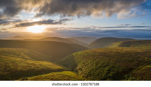 Aerial panoramic view over scenic hills at stormy dramatic sunrise. Shropshire Hills in United Kingdom