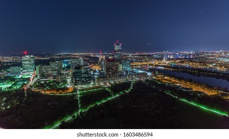 Aerial panoramic view over Vienna city with Donau City skyscrapers, historic buildings and a riverside promenade night timelapse in Austria. Illuminated skyline from Danube Tower viewpoint