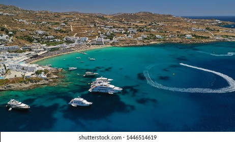 Aerial panoramic view photo of famous rocky seascape and celebrity sandy beach and bay of Platy Gialos with luxury yachts and expensive resorts, Mykonos island, Cyclades, Greece