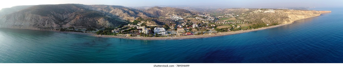 Aerial panoramic view of Pissouri bay, a village settlement between Limassol and Paphos in Cyprus. View of the coastline panorama, beach, hotel, resort, hills, plain and building developments.