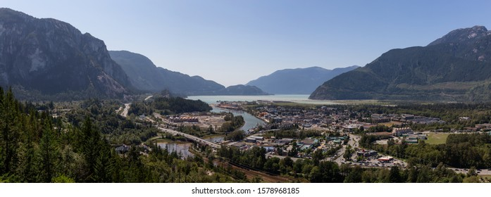 Aerial Panoramic view of residential homes in a small town with Chief Mountain in the background during a sunny summer day. Taken in Squamish, North of Vancouver, British Columbia, Canada.