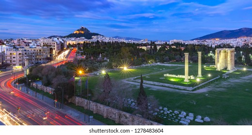Aerial panoramic view with Ruins and a columns of the Temple of Olympian Zeus, Mount Lycabettus at night, Athens, Greece